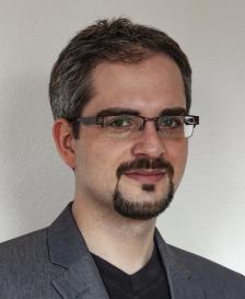 Ein lächelnder Mann im Anzug mit dunklem, angegrautem Bart, kurzem Haar und Brille.