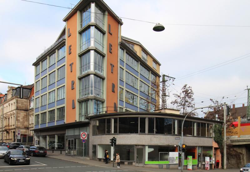 Ein viergeschossiges Eckhaus der Fünfzigerjahre mit großen Fensterflächen, Treppenhausturm und niedrigem Vorbau. Am Treppenhaus steht der Schriftzug Letra.