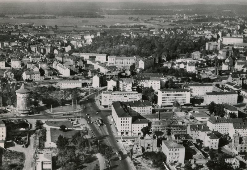 Vogelperspektive des Rathenauplatzes in Nürnberg in Schwarzweiß. Links steht ein alter Stadtmauerturm, weiter rechts vor allem moderne Neubauten aus den Fünfzigerjahren.